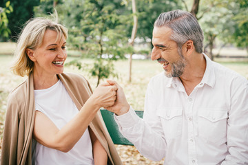 Elderly couple sitting on a bench tease each other having fun and laughing happily together at the public park in the morning. Happy concept of lifestyle in the retirement
