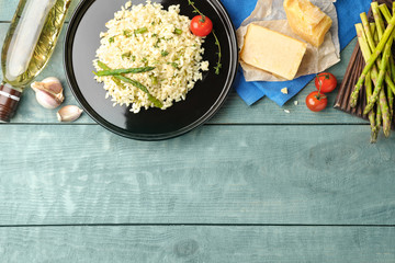Delicious risotto with asparagus served on blue wooden table, flat lay. Space for text
