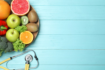 Foto op Plexiglas Keuken Fruits, vegetables and stethoscope on light blue wooden background, flat lay with space for text. Visiting nutritionist