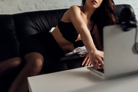 Cropped view of attractive girl in bra using laptop with web camera on sofa, selective focus