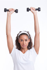 Portrait of young woman exercising with dumbbells against white background
