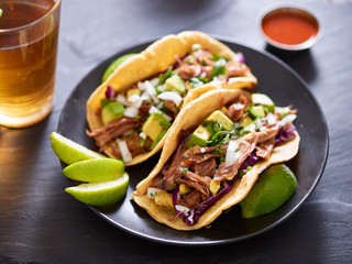 Wall Mural - mexican carnita street tacos with beer on slate table setting