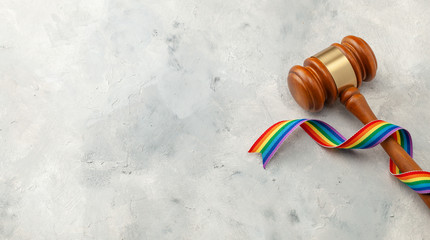 Judge gavel and rainbow ribbon of LGBT pride on gray background. Copy space for text