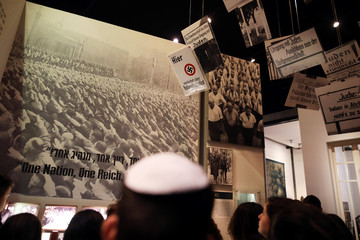 A man wearing a Yarmulke, or Jewish skullcap, is seen in the foreground as he looks at part of an exhibition in the Holocaust History Museum at the Yad Vashem World Holocaust Remembrance Center in Jerusalem