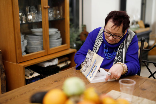 Holocaust survivor Vera Grossman Kriegel, 81, signs a book she wrote, during an interview with Reuters in Oranit, in the Israeli-occupied West Bank