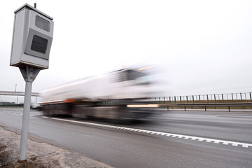 Police radar for measuring speed of passing vehicles stands on highway. Radar installed on roadside to control speed limit. Speed control, radar on the sideline controls speed of moving cars