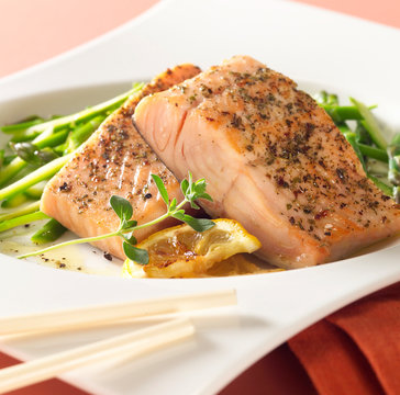 Closeup of herb covered baked tuna with a side of blanched asparagus