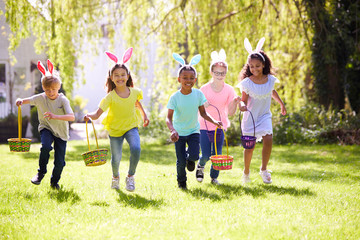 Papiers peints Ecole de Danse Group Of Children Wearing Bunny Ears Running To Pick Up Chocolate Egg On Easter Egg Hunt In Garden