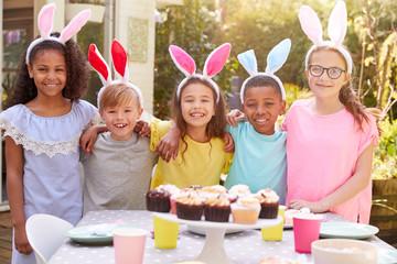 Portrait Of Children Wearing Bunny Ears Enjoying Outdoor Easter Party In Garden At Home