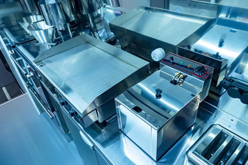 Cuisine of the restaurant. Concept - restaurant cleaning services. Purity. Equipment for food production. Equipment for restaurants. Electric frying pan top view. Toaster. Deep fryer in a cafe.