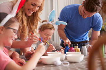 Parents With Children Wearing Bunny Ears Sitting At Table Decorating Eggs For Easter At Home