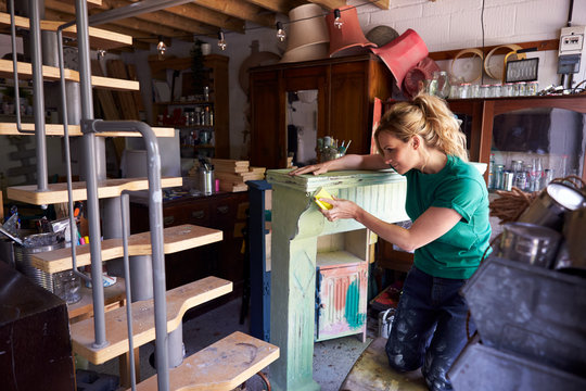Woman In Workshop Upcycling And Working On Fire Surround