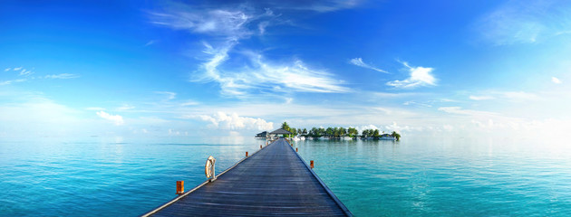 Beautiful tropical landscape background, concept for summer travel and vacation. Wooden pier to an island in ocean against blue sky with white clouds, panoramic view.