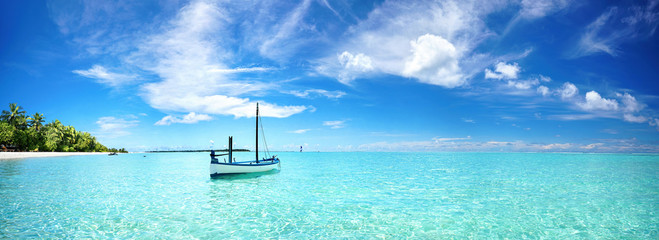 Boat in turquoise ocean water against blue sky with white clouds and tropical island. Natural landscape for summer vacation, panoramic view.