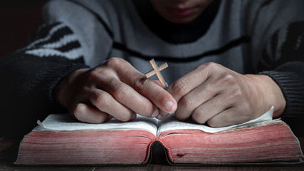 Praying hands of male with the silver Cross on holy bible. christian concept.