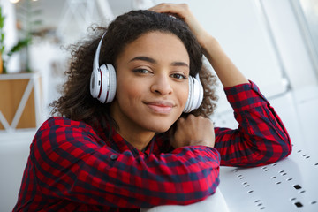 Portrait of african american woman listening to music with headphones