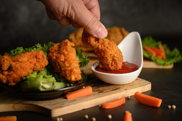 Hand holding crispy fried chicken dipped in tomato sauce.