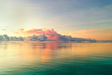 Beautiful cloud over ocean water at sunset in Golden pink blue and green tones. Colorful natural...