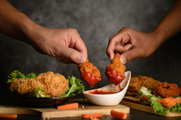Two hand holding crispy fried chicken dipped in tomato sauce