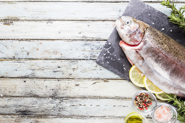 Raw trout fish on slate with rosemary and lemon over white wooden table, top view