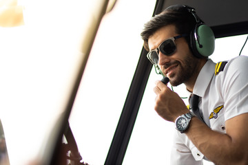 Pilot with headset starting the controls in cockpit helicopter. Helicopter pilot sitting in the cockpit. exclusive travel and business concept Wall mural