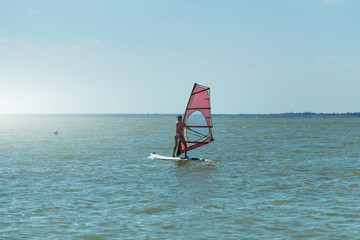 Young athletic slim girl sails on a windsurf board in the open sea on summer vacation at resort. Windsurfing