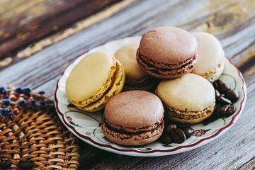 Aluminium Prints Macarons Macarons praline vanille café chocolat sur une coupelle en céramique