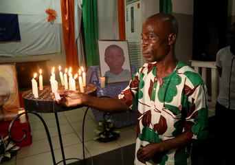Marius Ani Oulakole, father of Barthelemy Laurent Guibahi Ani, a 14 years old boy who were found dead in the undercarriage of an Air France airplane, lights a candle during a tribute prayer to his son in Abidjan
