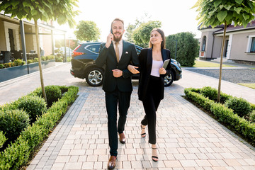 Full-lengh portrait of business people, caucasian lady and man talking phone walking together for important business meeting presentation. Outdoors at the yard of business center, near black car