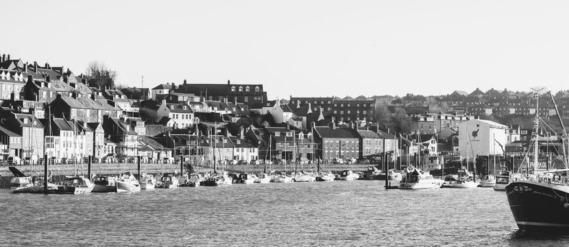 Whitby, North Yorkshire, England - Jan 28, 2019:,UK - Black and white photo  of The harbour at Whitby on the North Yorkshire coast, Fishing boats tied up to the quay in Whitby harbour