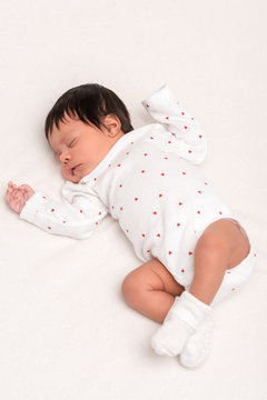overhead view of bi-racial newborn in baby romper and socks sleeping isolated on white