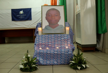 A poster of Barthelemy Laurent Guibahi Ani, a 14 years old boy who was found dead in the undercarriage of an Air France plane, is seen flanked by candles during a tribute prayer in Abidjan