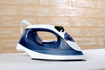 New modern electric steam iron on ironing board