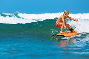 Happy boy - young surfer learning ride, jump from surfboard with fun, run to beach. Active family lifestyle. Kids surf lessons, outdoor water sport activity in surfing camp. Summer vacation with child