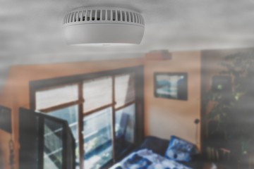 Domestic smoke alarm / battery powered smoke detector on the ceiling in room filled with smoke from fire at home