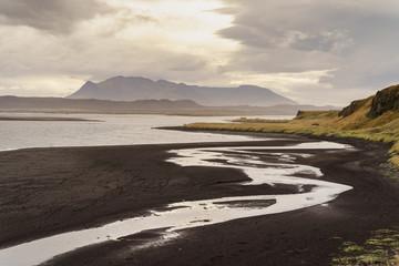 Dusk on the black sand beach before a mountain range on a gloomy day -- Iceland
