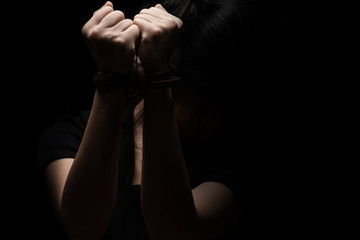Woman tied up with leather belt in emotional stress and pain