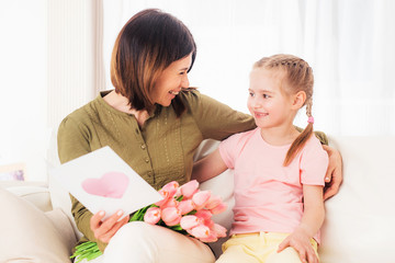 Beatiful mom likes opening nice daughters presents for Mothers day