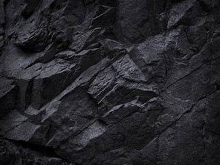 Mountain background texture. Close-up. Black rock background. Dark gray stone background. Black and white background. Black grunge texture. Contrast monochrome rocky texture.