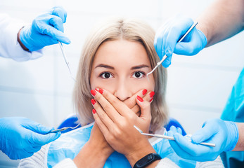 Scared blond girl in dentistry close her mouth