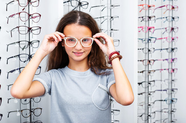 Smiling teenage girl with pretty white glasses standing in the optical store