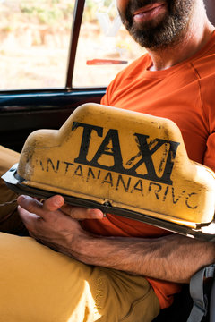 Unrecognizable tourist sitting inside a taxi with taxi panel in his hand, Antananarivo, Madagascar