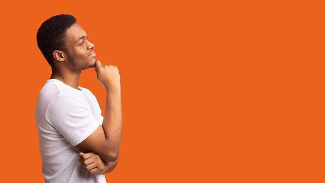 Pensive afro man profile portrait on orange background