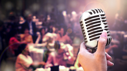 Retro microphone in women hand for speech or singing isolated on black background