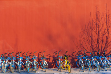 Photo sur Aluminium Pekin Beijing, China-31 December 2019, Row of share bikes parking on footpath with red wall in Beijijng city, China.