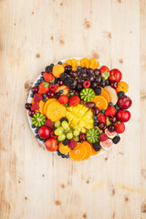 Wall Mural - Healthy fruit platter, strawberries raspberries oranges plums apples kiwis grapes blueberries mango persimmon on wooden table, top view, copy space for text, selective focus