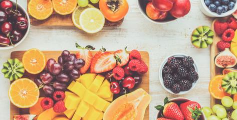 Wall Mural - Healthy breakfast, cut colorful rainbow fruits, strawberries raspberries oranges plums apples kiwis grapes blueberries mango persimmon, copy space, toned, banner, selective focus