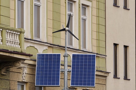 Street electricity by small windmill and solar panels in the city against buildings in daytime. Concept of renewable, eco or environmentally friendly and clean energy