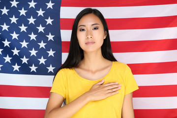 Young woman with hand on chest on American flag background