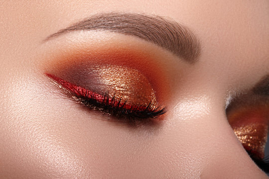 Fashion Celebrate Makeup with Red Liner, Gold Shadows, Glowy Clean Skin, perfect Shapes of Brows. Macro of Female Eye